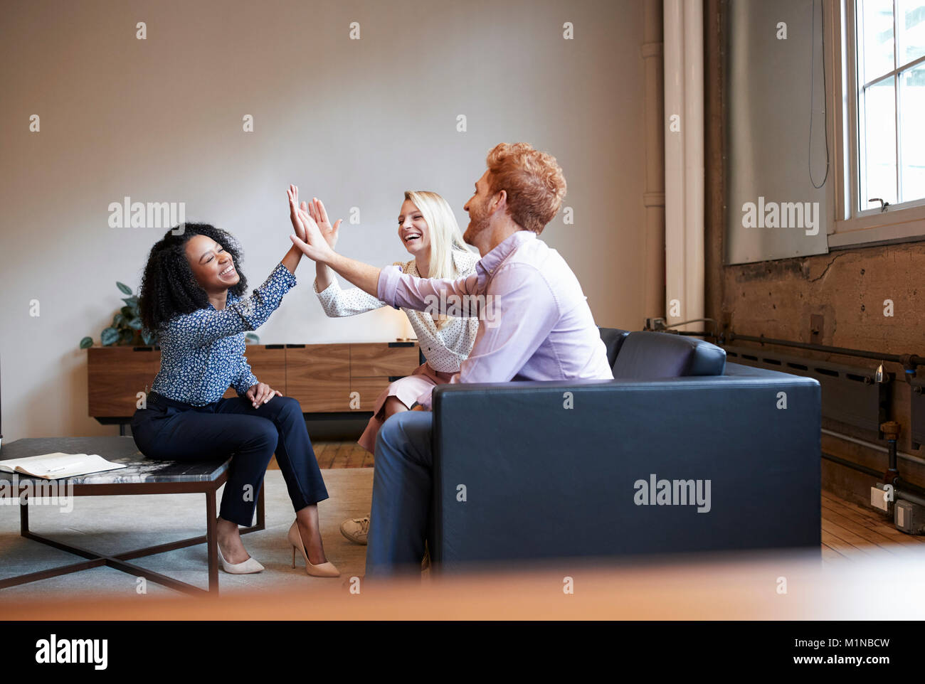 Three colleagues high five at a casual work meeting Stock Photo