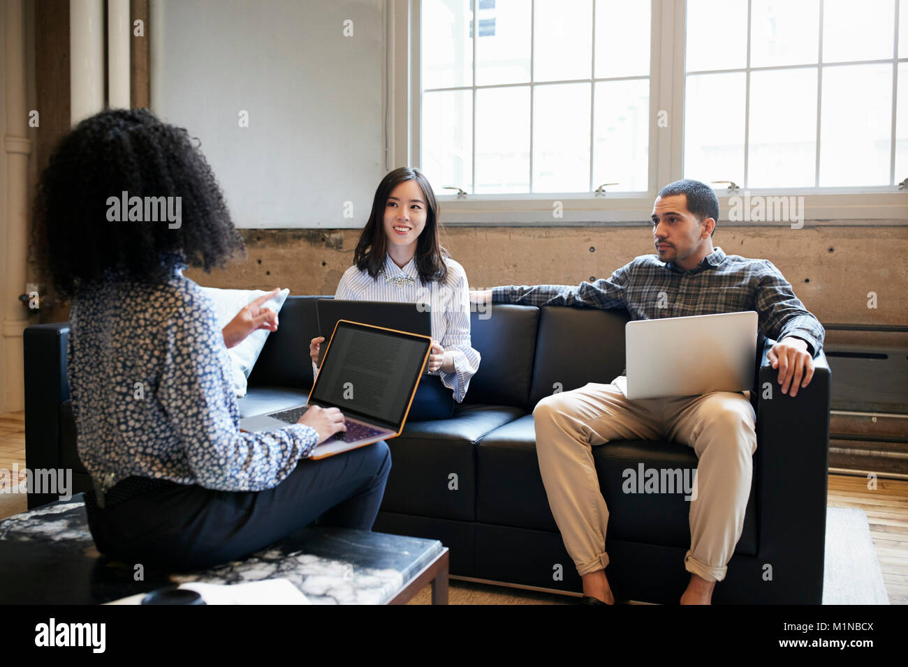 Three young colleagues with laptops at a casual work meeting - Stock Image
