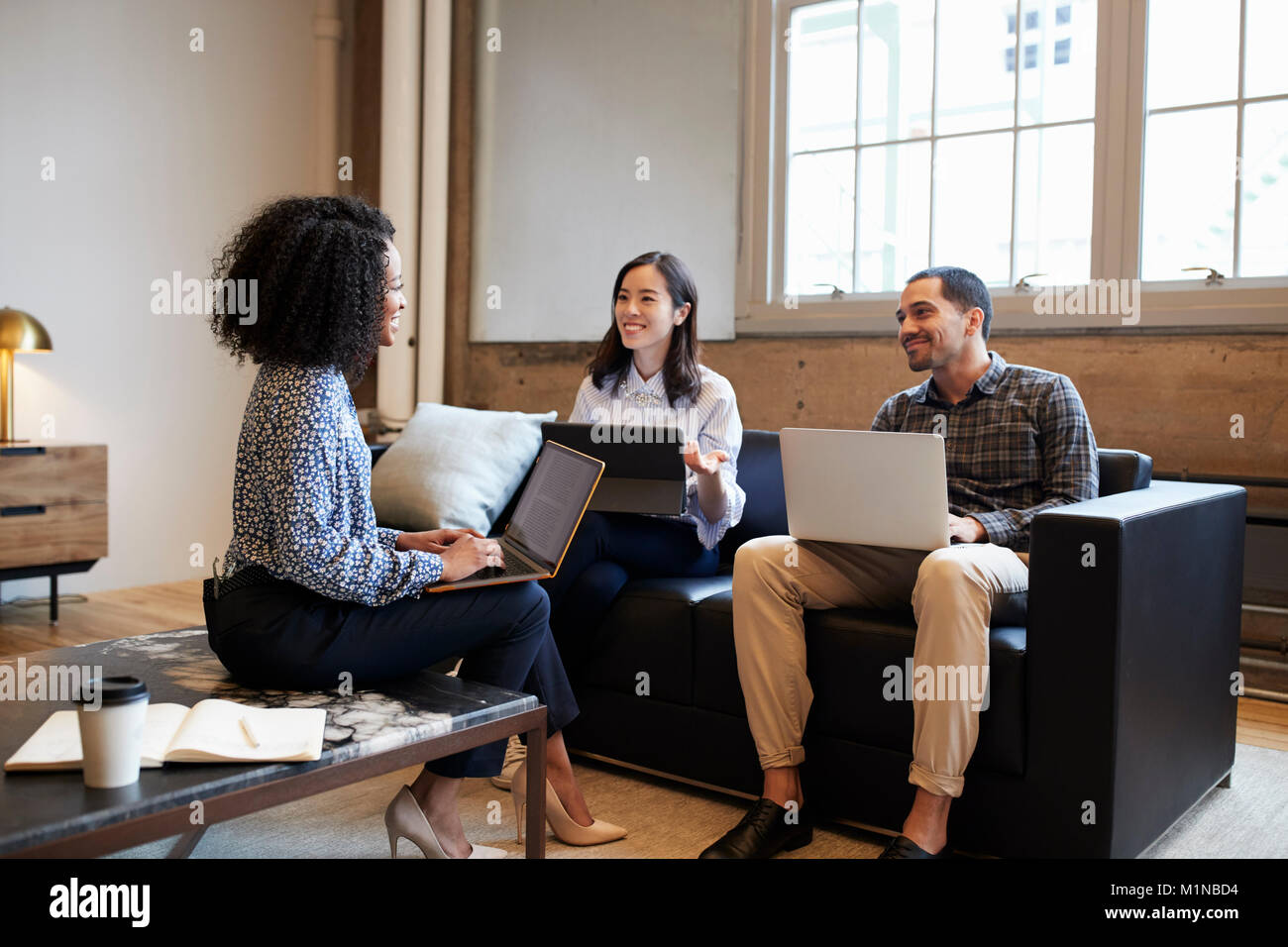 Smiling work colleagues with laptops at a casual meeting - Stock Image
