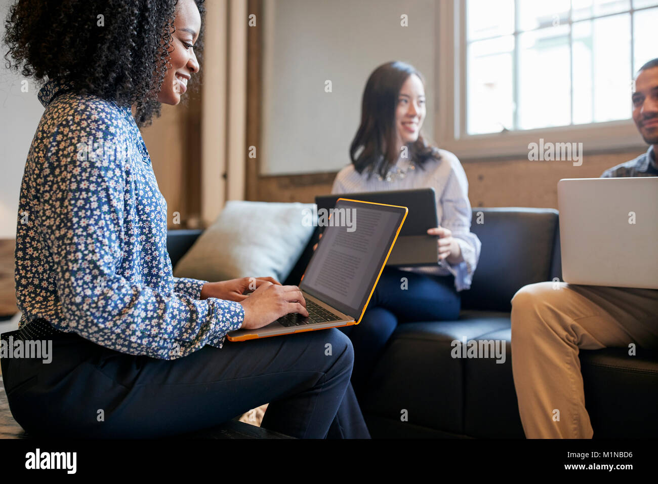Smiling colleagues working together with laptops, close up - Stock Image