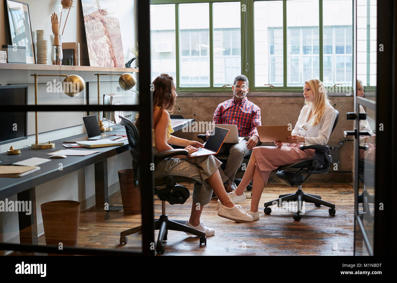 Business team meeting in an office booth, close up - Stock Image