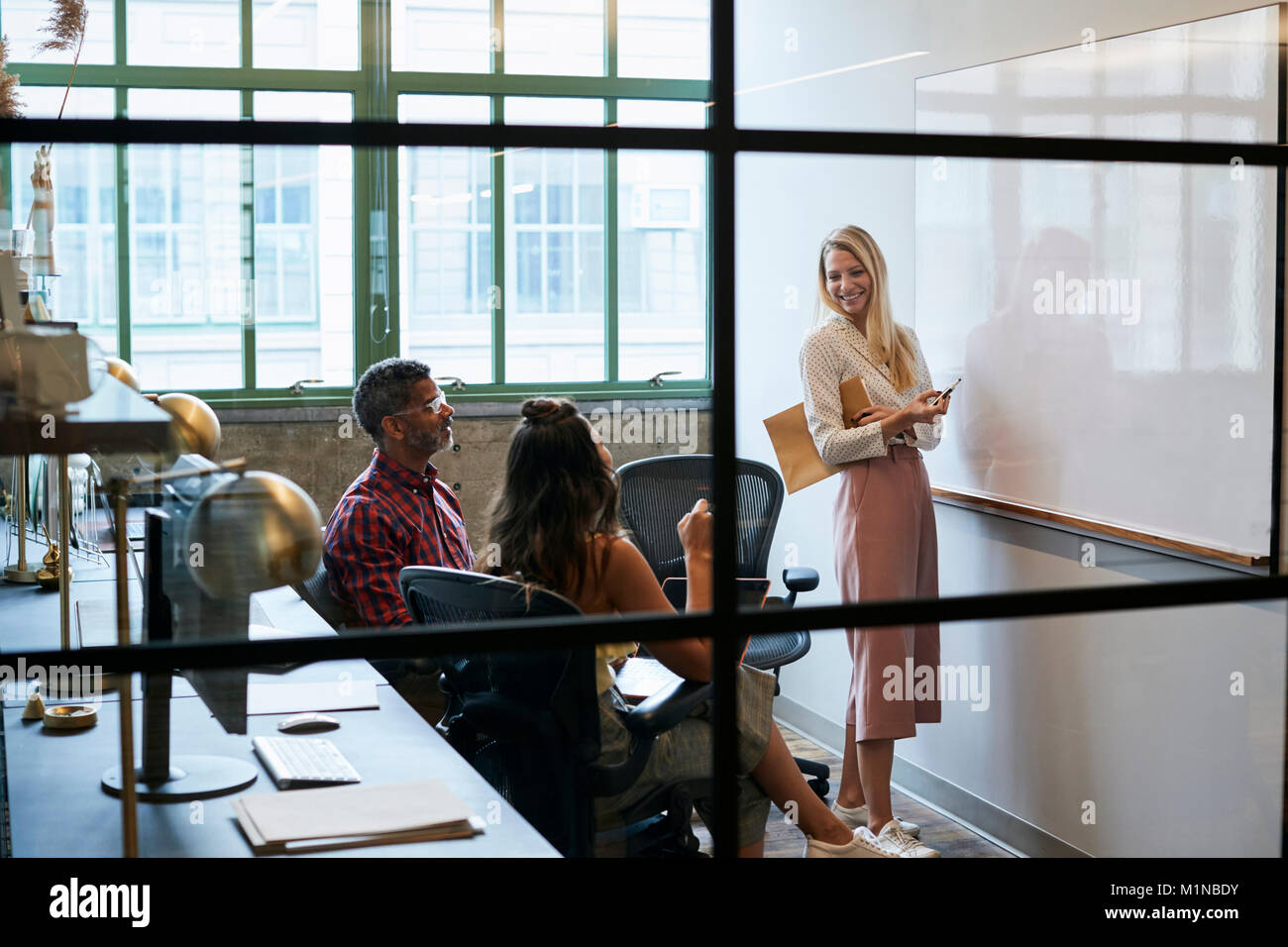 Woman at whiteboard in team meeting, seen through glass wall - Stock Image