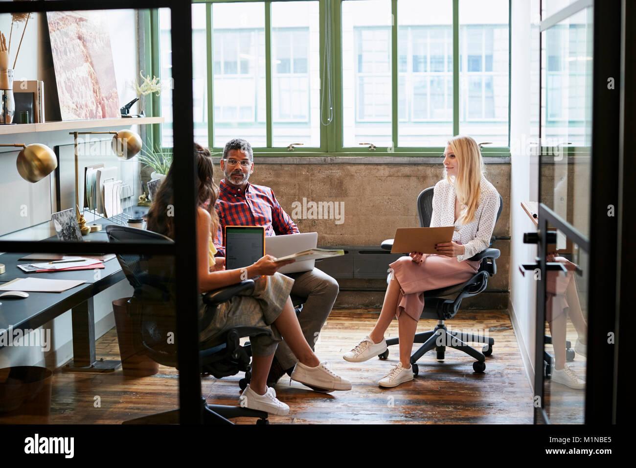 Three coworkers in a team meeting, seen through open door - Stock Image