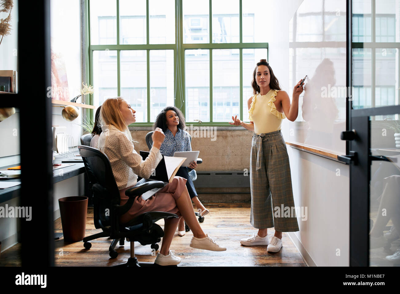 Woman looking to whiteboard in a meeting with female team - Stock Image