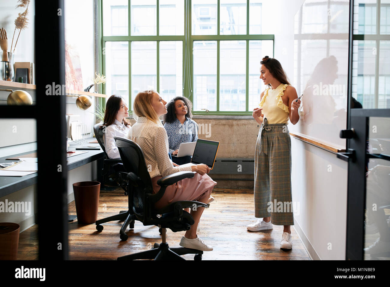 Woman standing at whiteboard in a meeting with female team - Stock Image