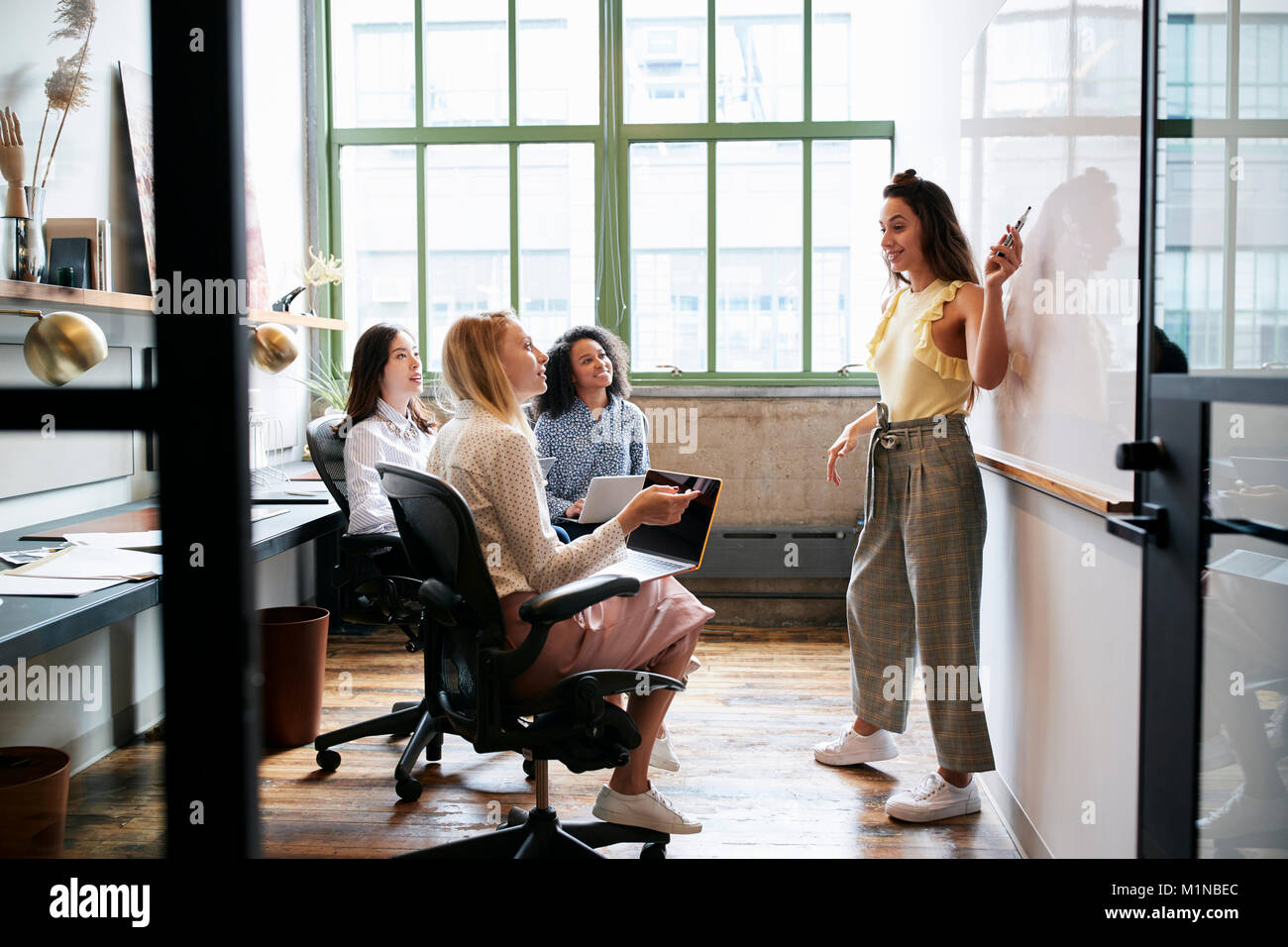 Woman pointing at whiteboard in a meeting with female team - Stock Image