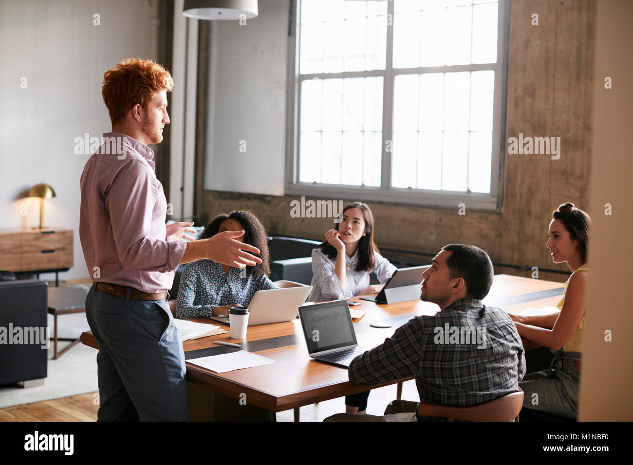 Young man standing to address colleagues at a work meeting - Stock Image