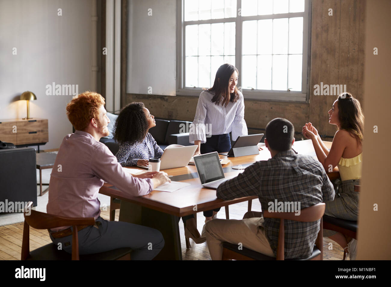 Young woman standing to address colleagues at a work meeting - Stock Image