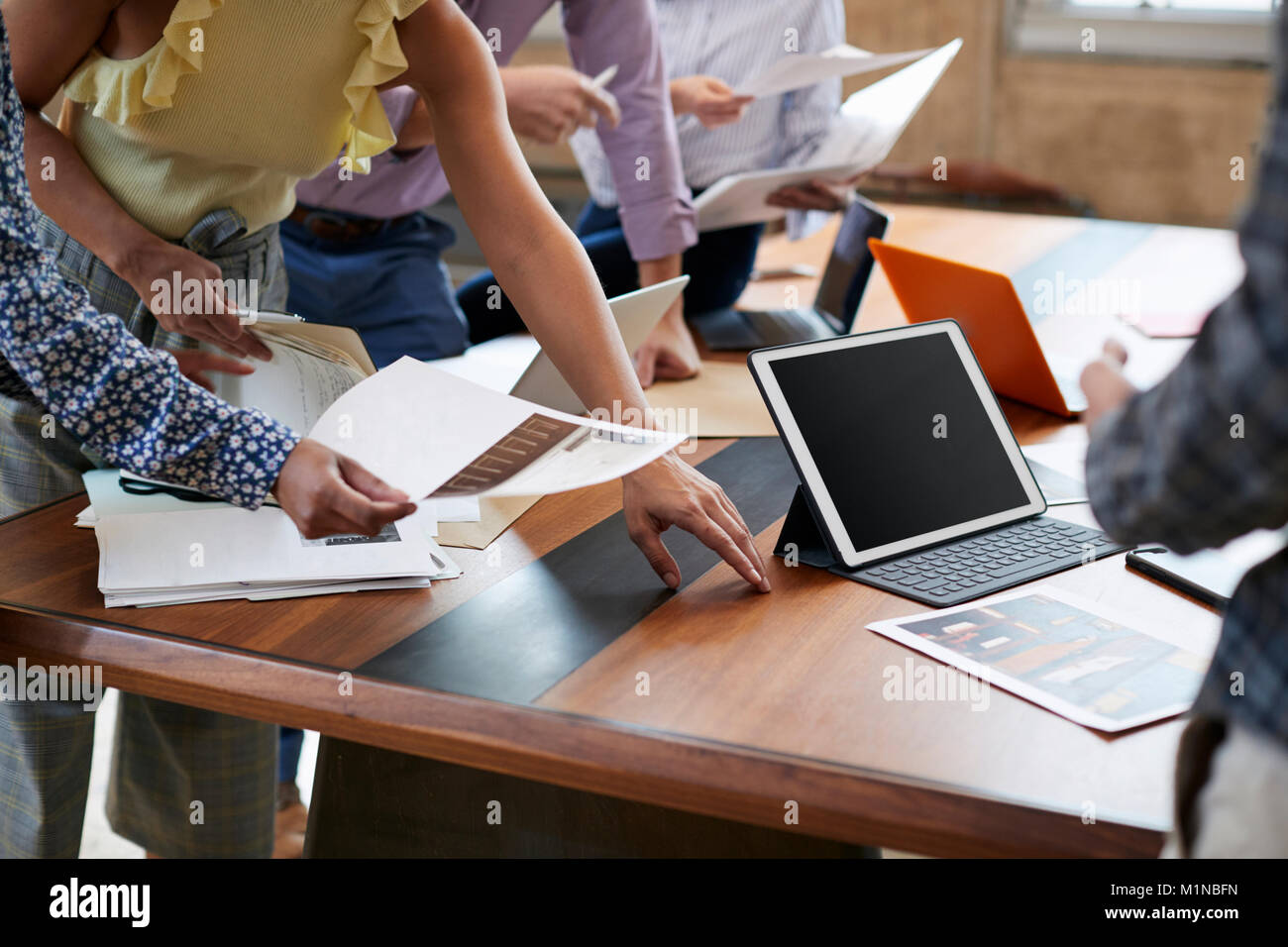Creatives brainstorming ideas around a table, mid section - Stock Image