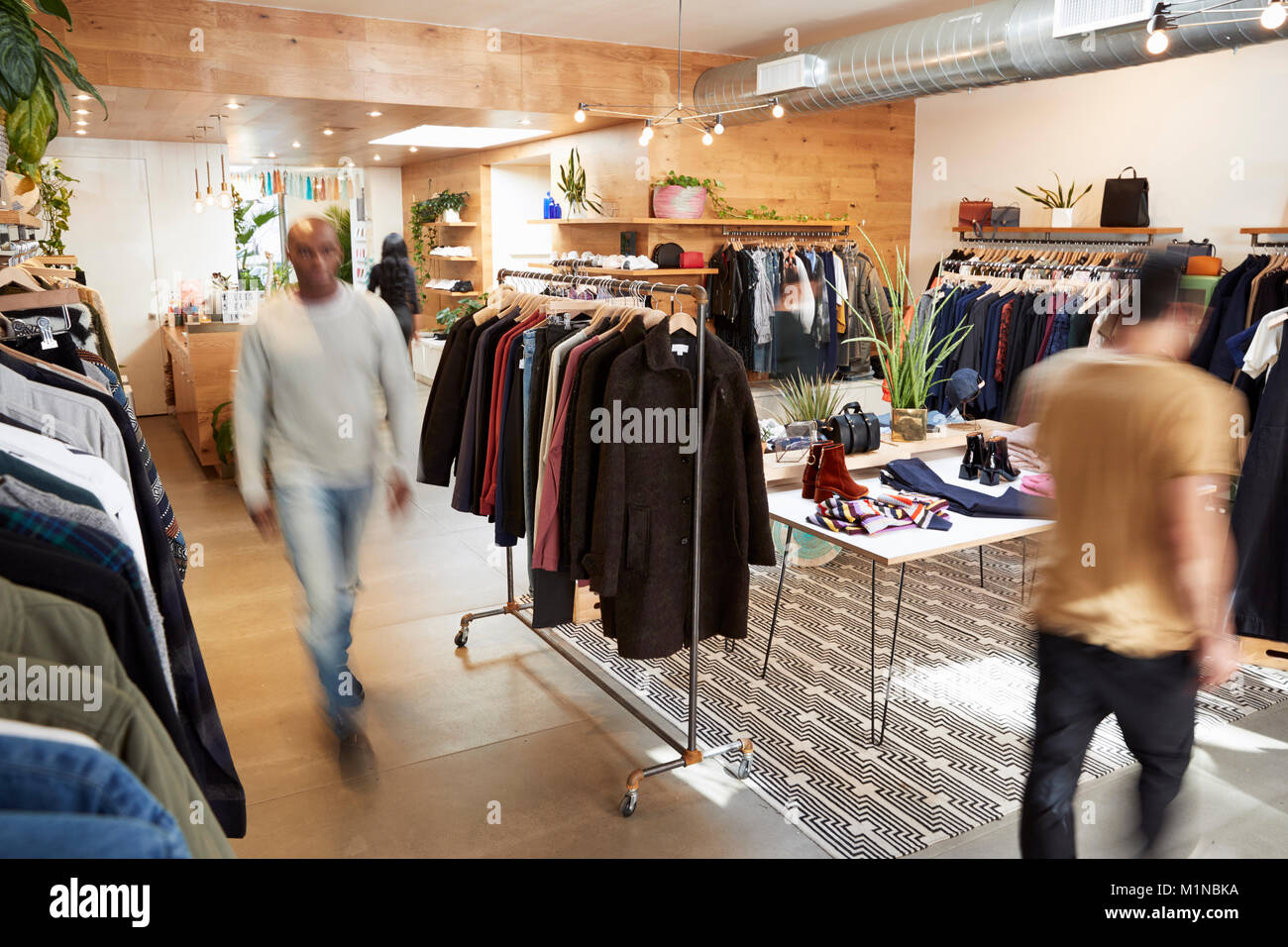 People walking through a busy clothes shop, motion blur - Stock Image