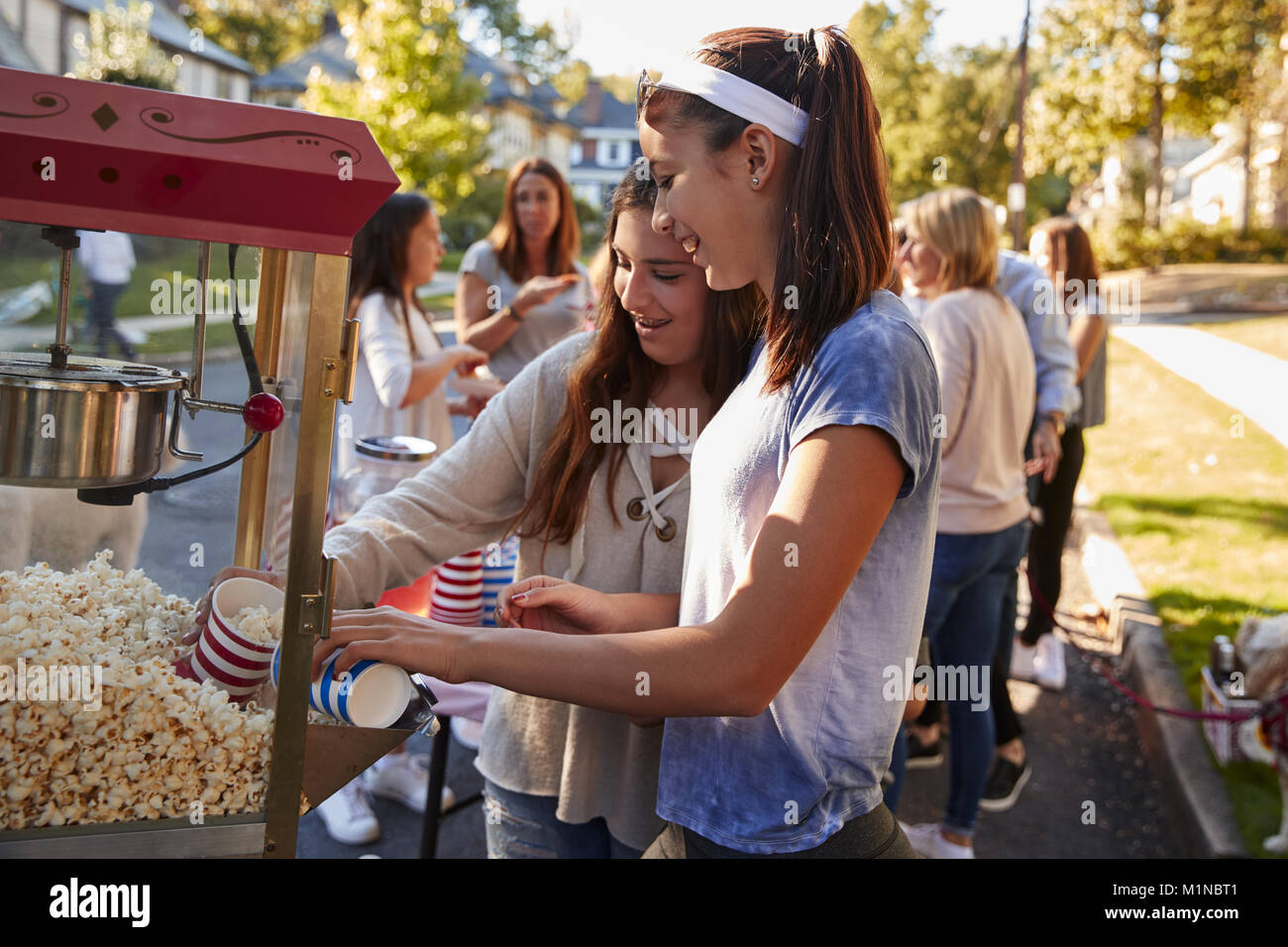 Girls serve themselves popcorn at neighbourhood block party - Stock Image