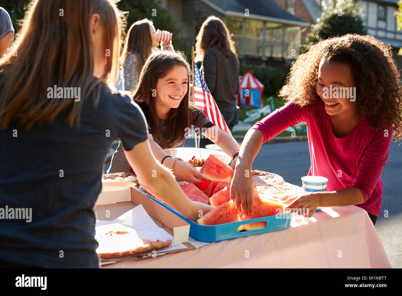 Girls serving themselves watermelon at a block party - Stock Image