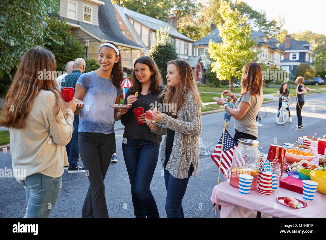 Teenagers talking in the street at a block party - Stock Image