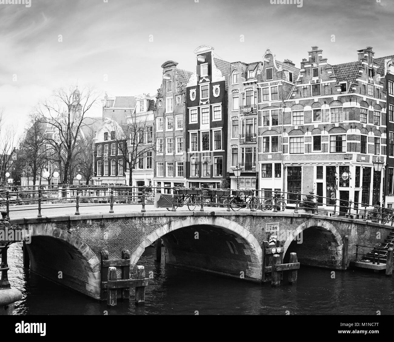 Prinsengracht Canal, Amsterdam, The Netherlands. Typical  Dutch houses  with a crow-stepped gable  behind the bridge. - Stock Image
