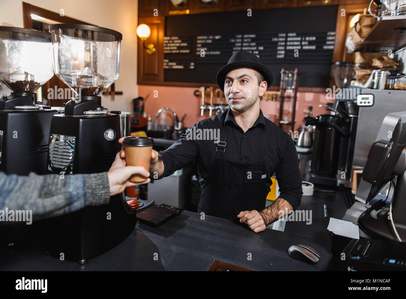Positive barista male selling coffee to a consumer in a coffee shop. - Stock Image
