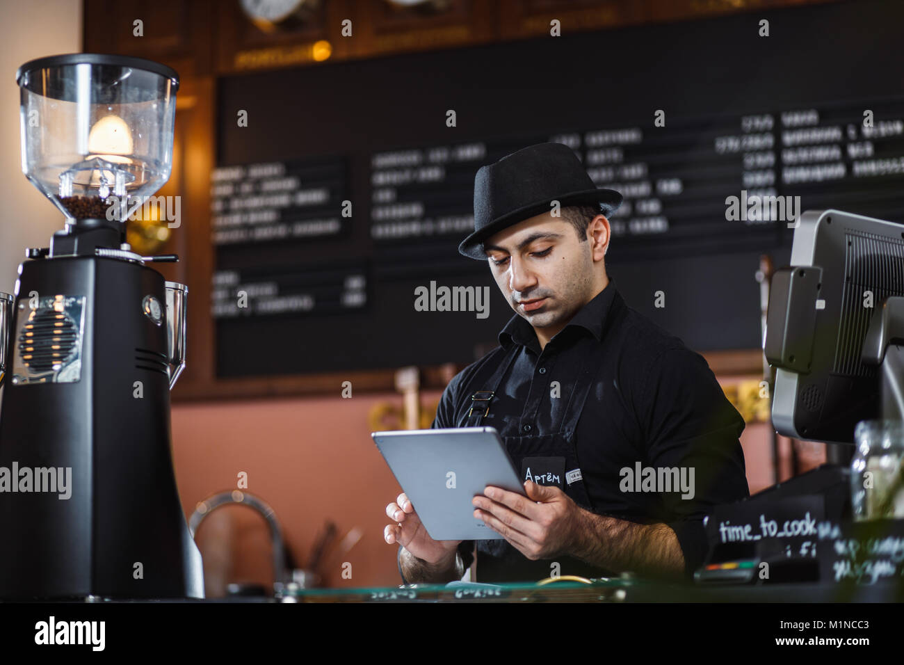 Portrait of barista holding digital tablet at counter in coffee shop. - Stock Image