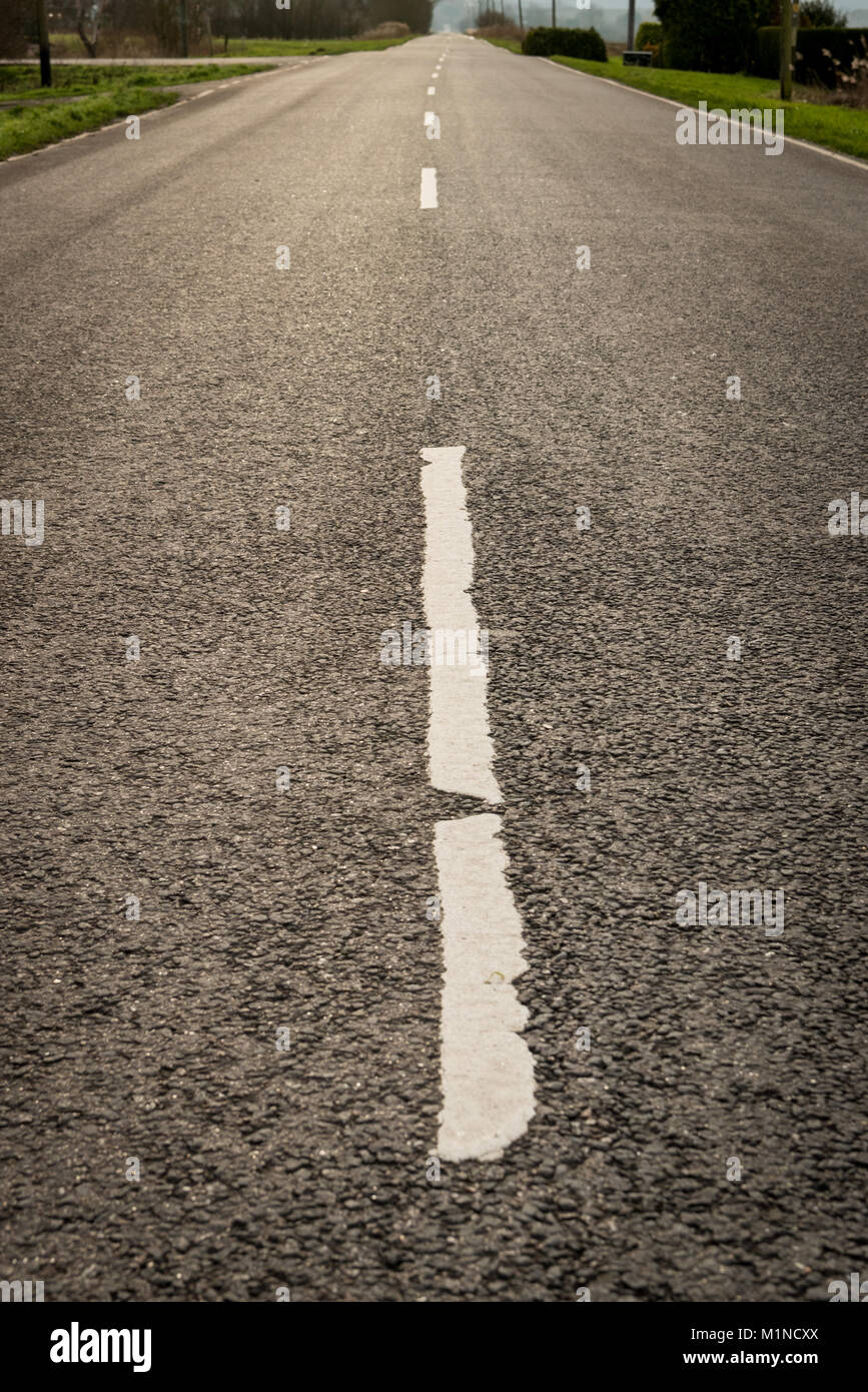 A white line on a straight tarmac road in the UK Fens with the horizon and vanishing point in the distance - Stock Image
