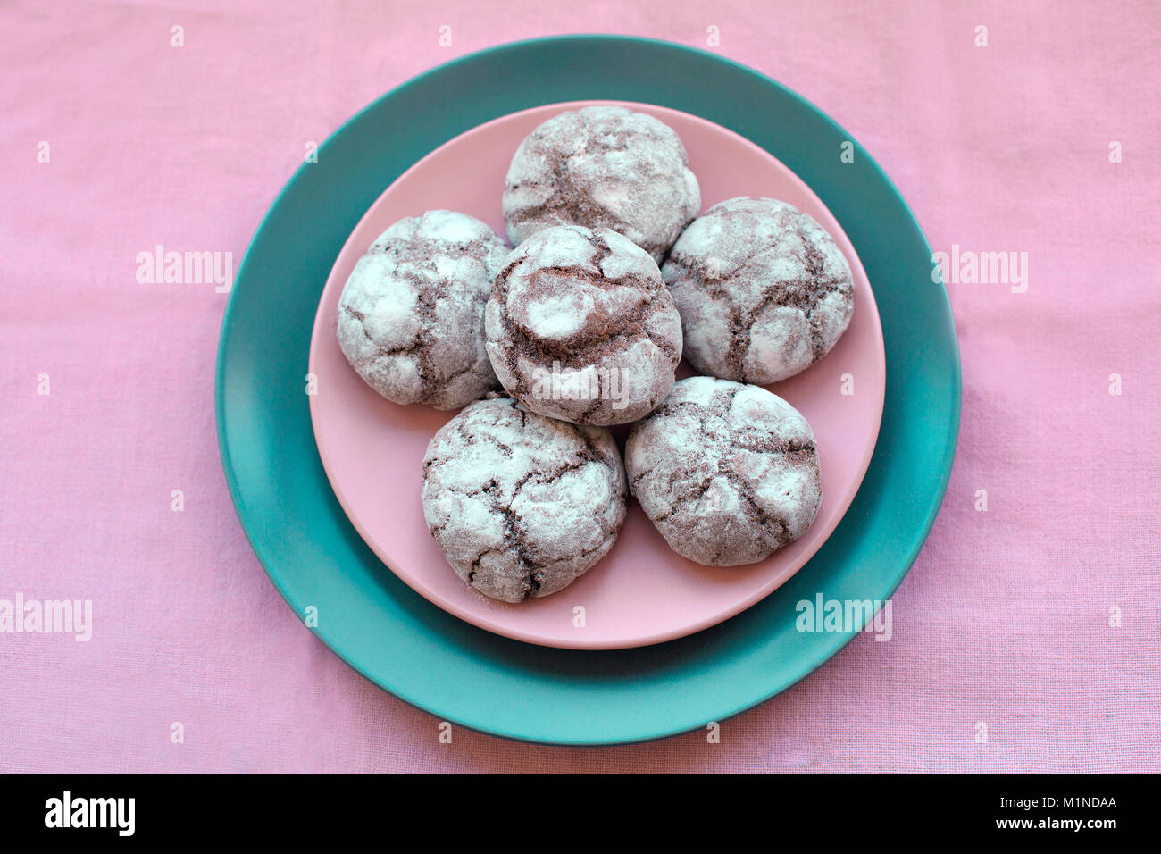 Chocolate cookies on plate onpink tablecloth, top view. Food, junk-food, culinary, baking and eating concept. - Stock Image