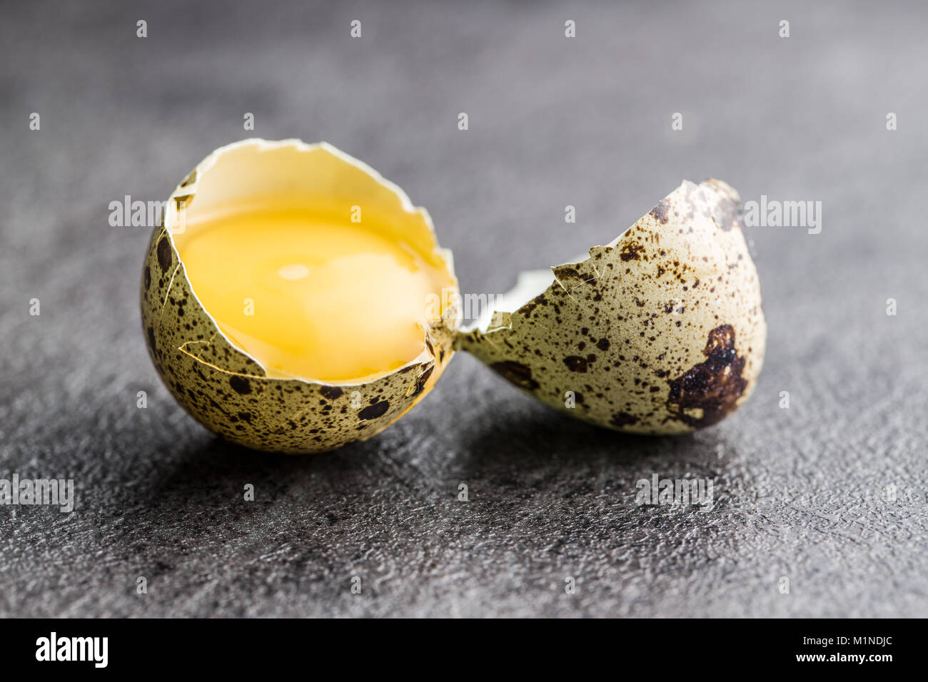 Broken guail eggs on old kitchen table. - Stock Image