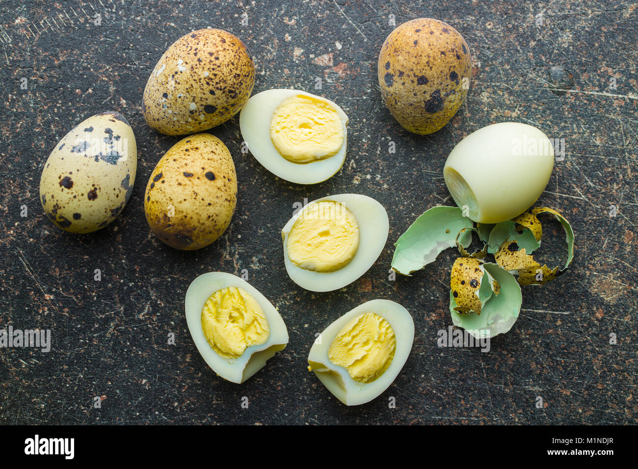 Boiled guail eggs on old kitchen table. - Stock Image