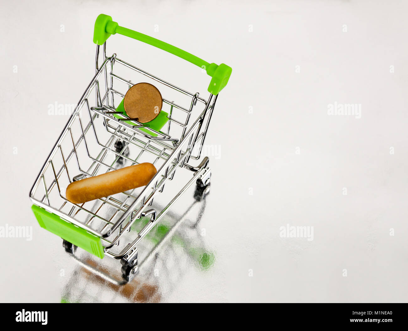 A supermarket trolley with a loaf of bread and a coin - Stock Image