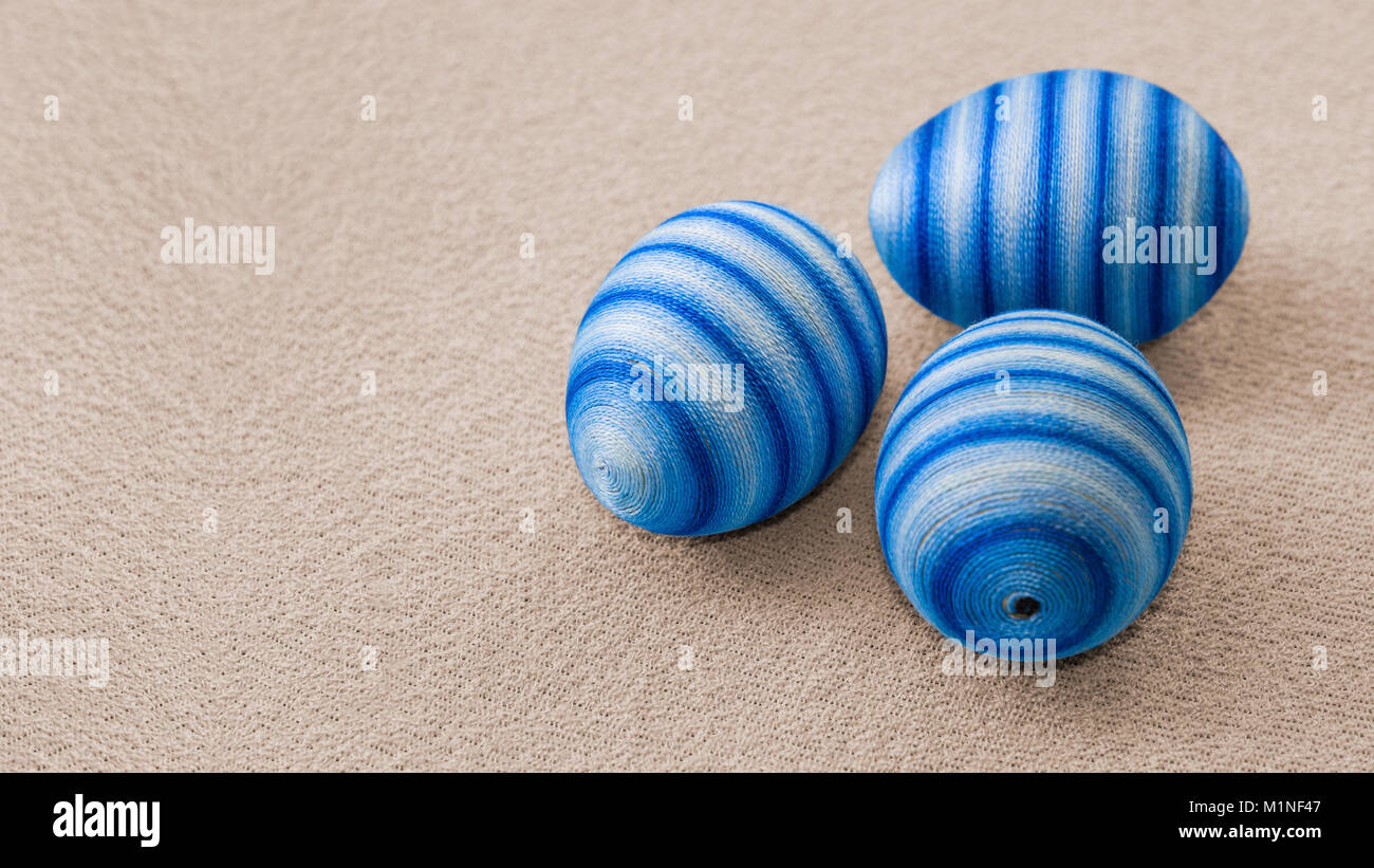 Three blue hand-decorated easter eggs. Creative decoration ornated by glued cotton yarn on a brown textile background. - Stock Image