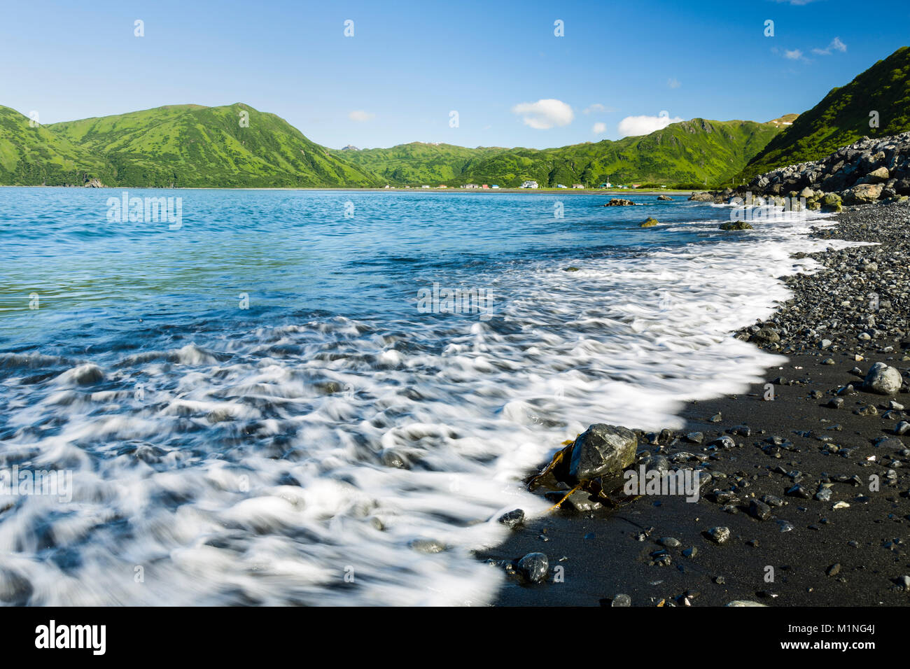 Waves wash ashore at Pasagshak Bay with the village of Pasagshak in the background on Kodiak Island in Southwestern - Stock Image