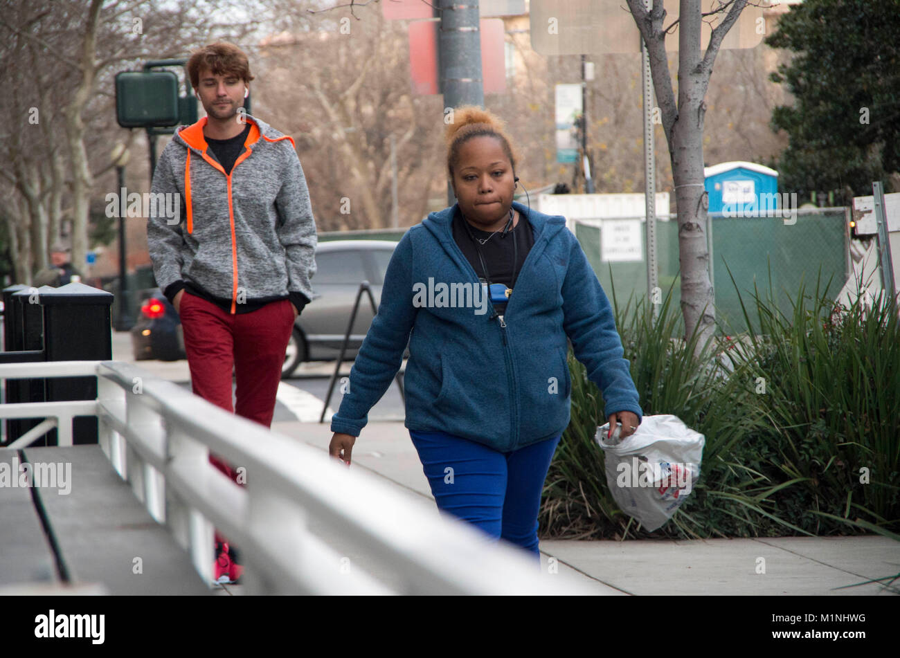 Two people take a walk on 9th Street in Sacramento. - Stock Image