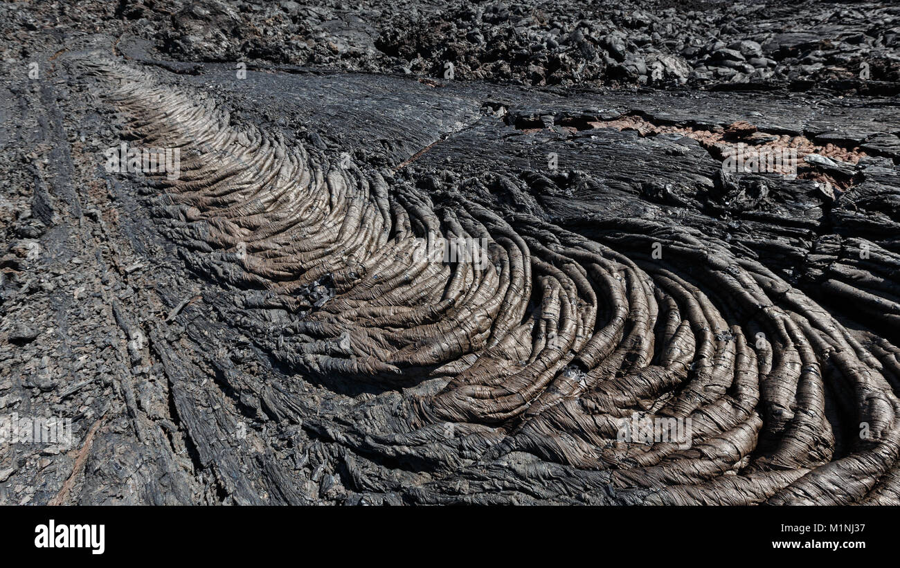 Lava field volcano landscape: smooth, undulating surface of frozen lava flow, which wrinkled in tapestry-like folds - Stock Image