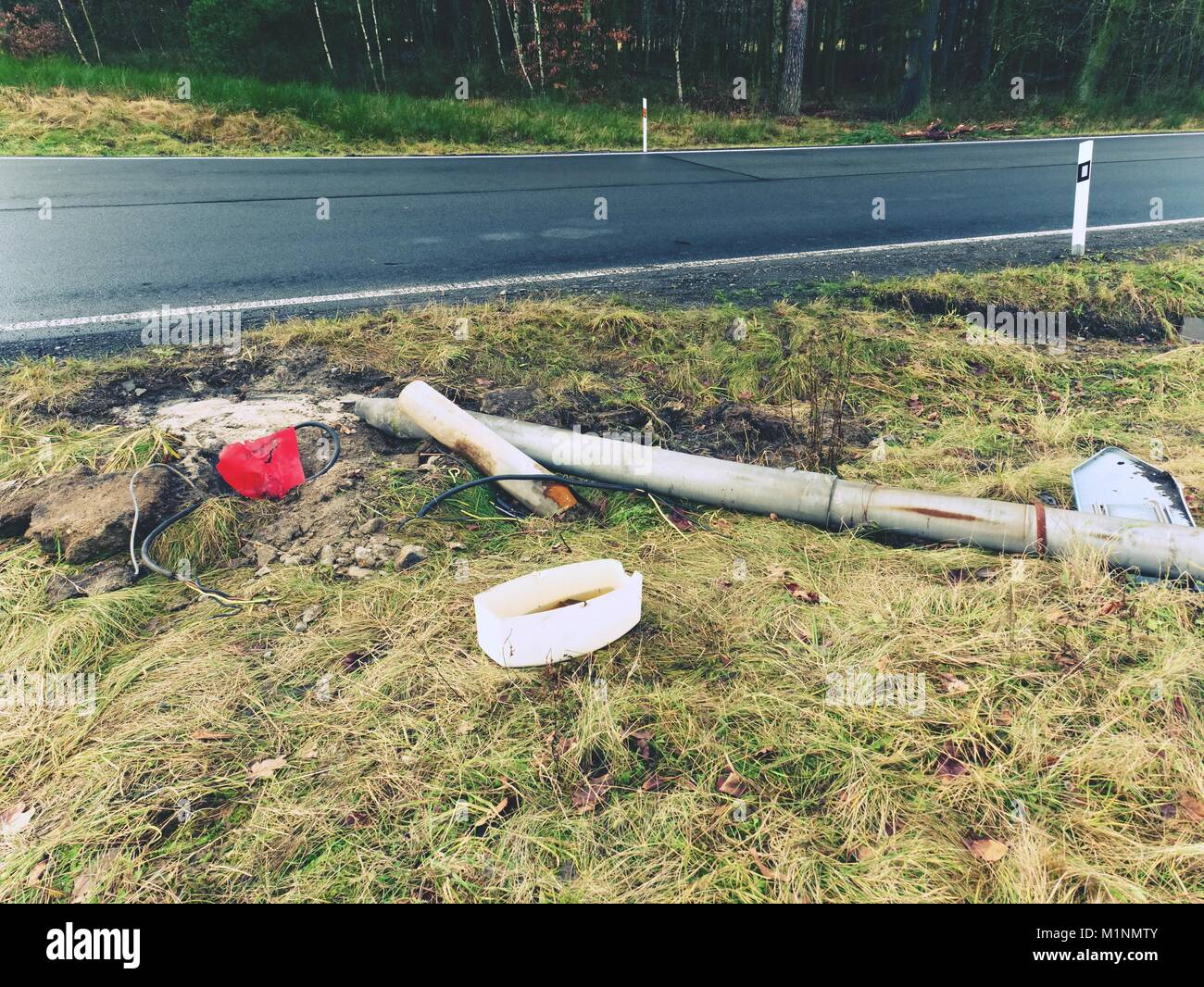 Broken lamp post after car accident. Freeze morning  with slippery asphalt road. January cold and rainy weather - Stock Image