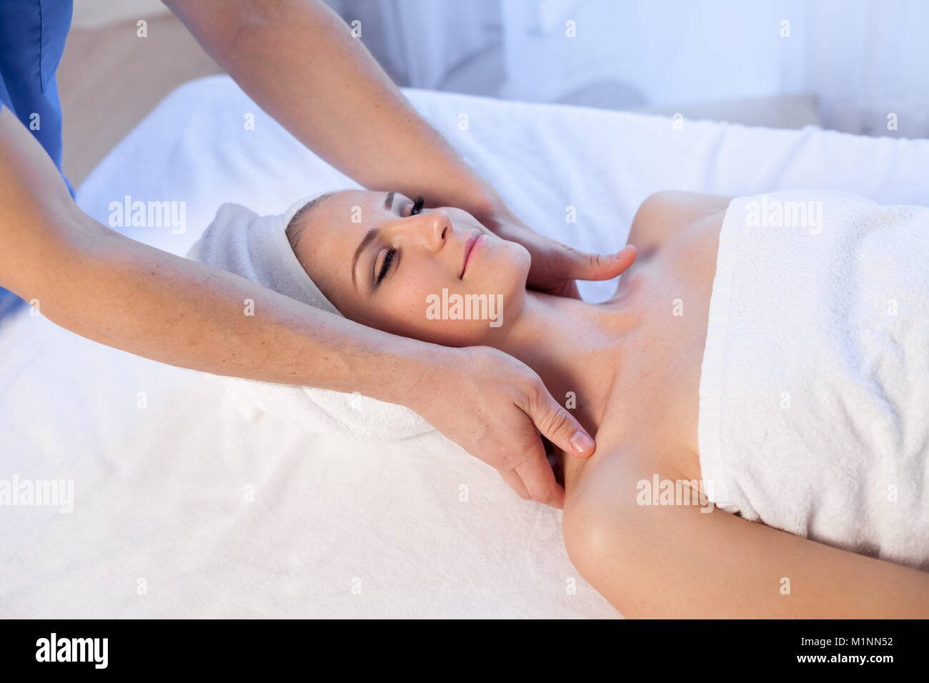 doctor cosmetologist doing facial massage girl spa treatments - Stock Image