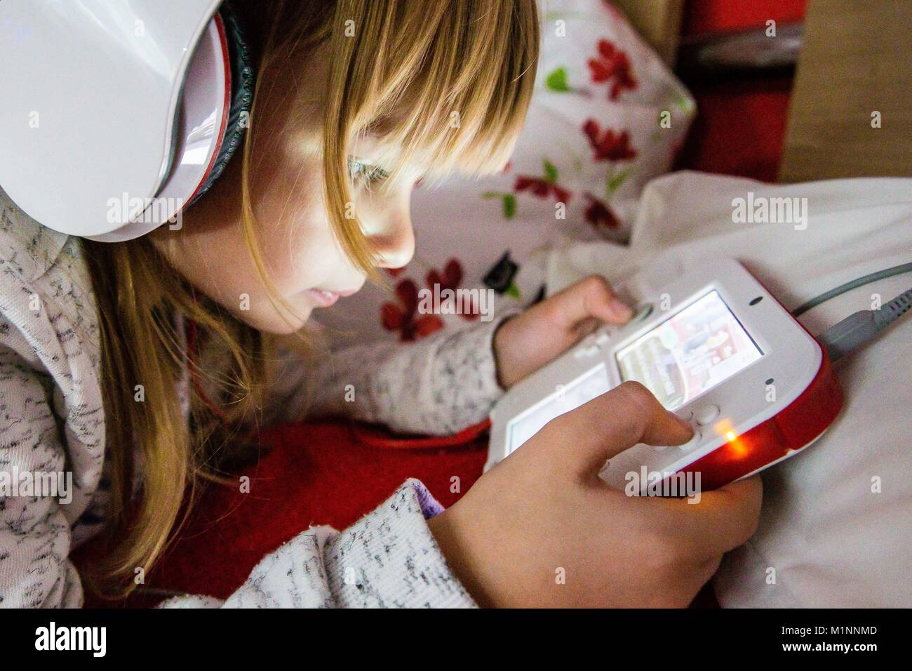 6 year old girl with headphone on plays with a Nintendo DS on a bed, Kernen, Germany, Nov. 5, 2017. | usage worldwide - Stock Image