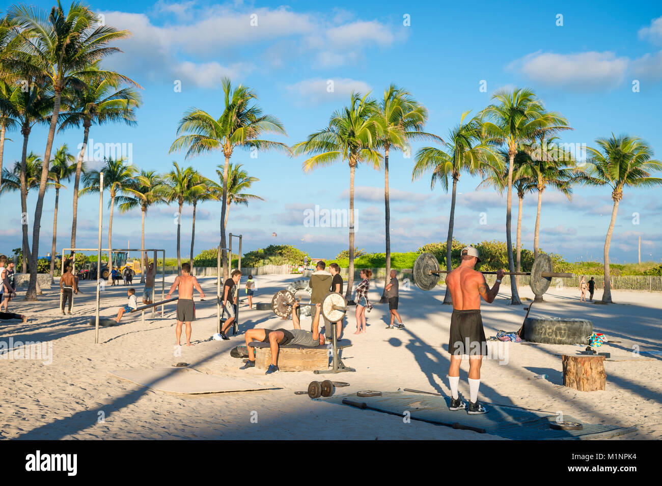 MIAMI - DECEMBER 27, 2017: Muscular young men work out at the outdoor workout station in Lummus Park known as Muscle - Stock Image