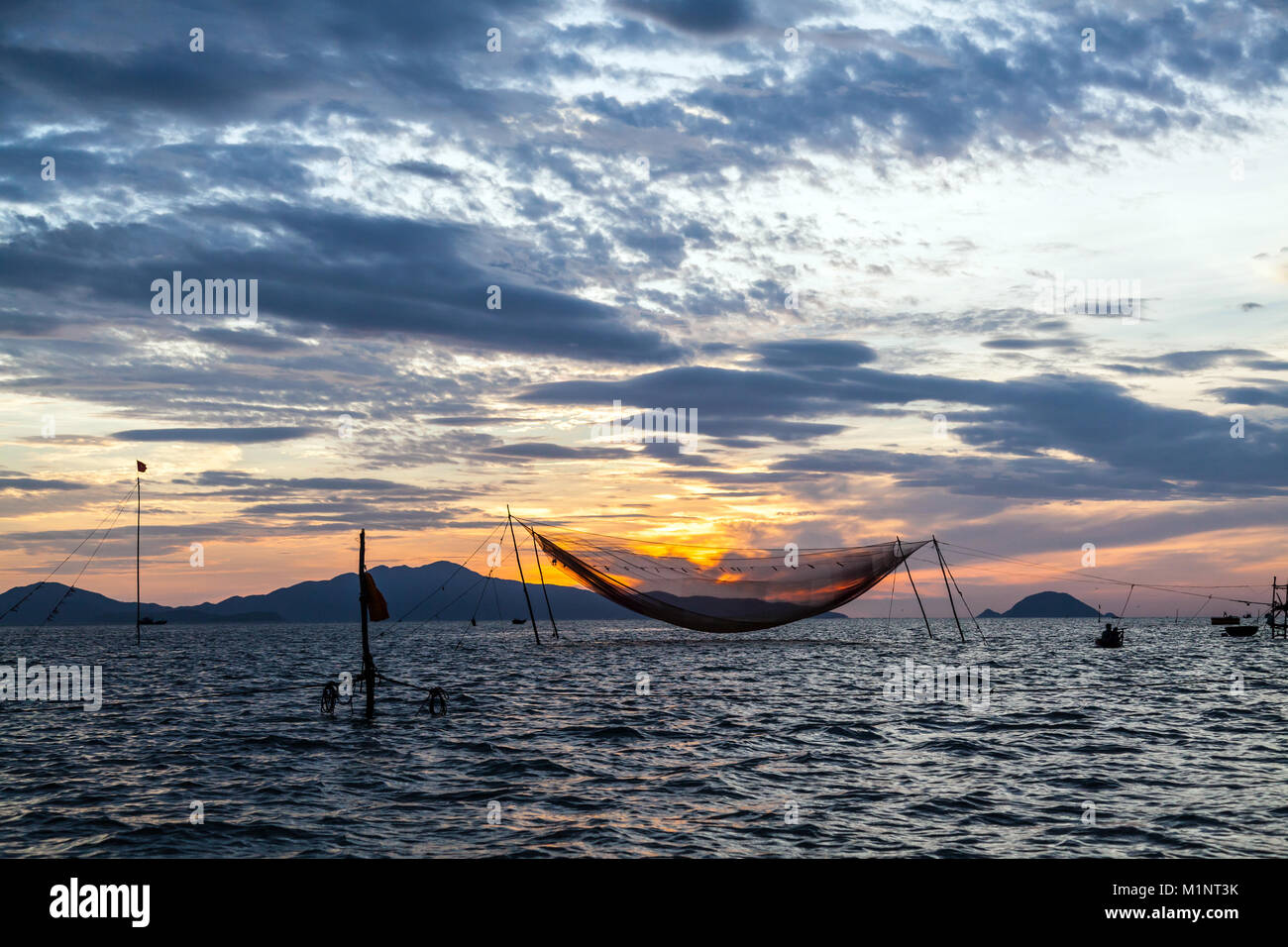 Sunrise over a traditional hanging fishing net in the sea, at the entrance to Thu Bon River, near Hoi An, Vietnam - Stock Image