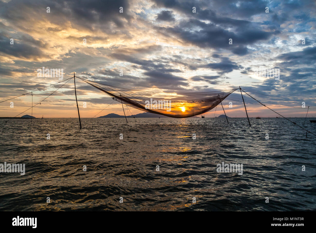 Sunrise over a traditional hanging fishing net in the sea, at the entrance to Thu Bon River, Hoi An, Vietnam - Stock Image