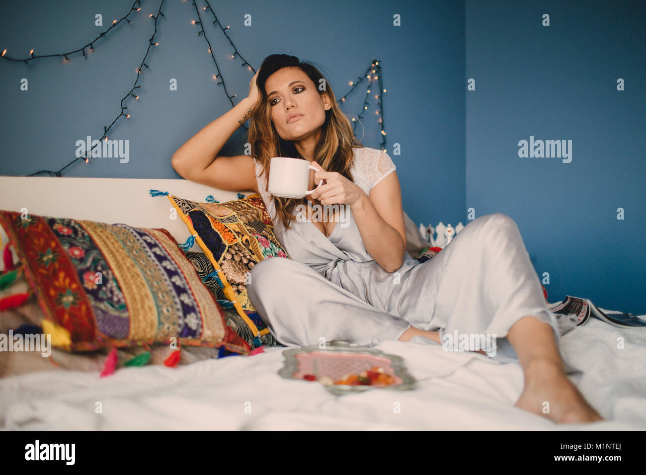 Young beautiful woman drink coffee at home lying on bed. - Stock Image