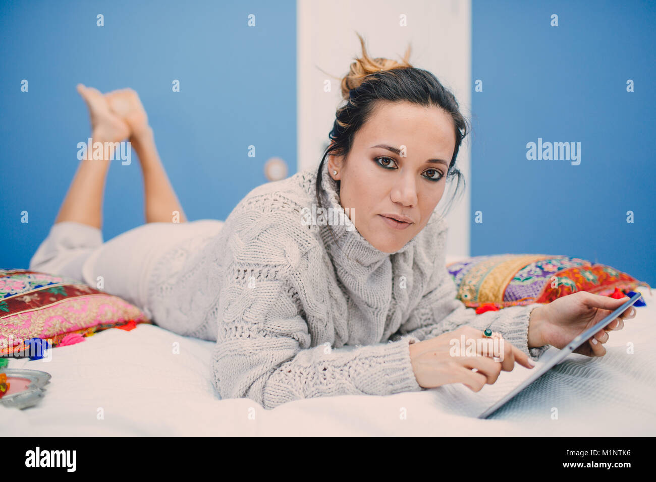 Young beautiful woman reading tablet at home lying on bed. - Stock Image