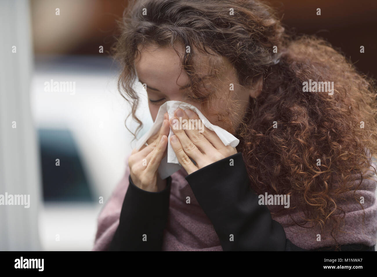 Woman blowing her runny nose or sneezing in a paper tissue outside on the street - Stock Image