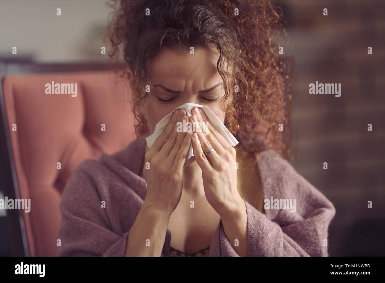 Woman blowing her runny nose or sneezing in a paper tissue - Stock Image