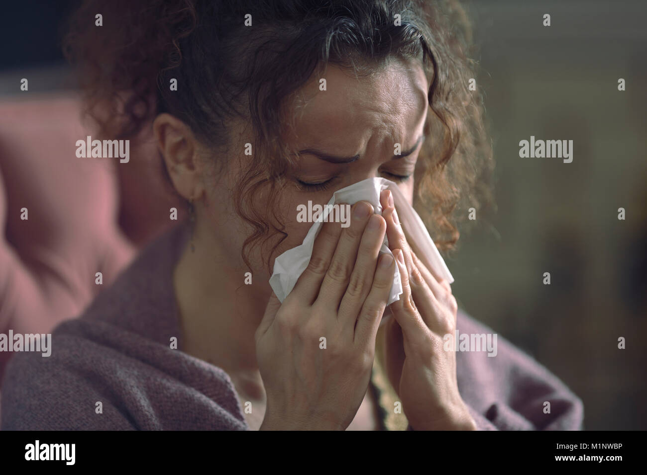 Closeup portrait of a woman with a miserable sick expression blowing her runny nose in a paper tissue - Stock Image