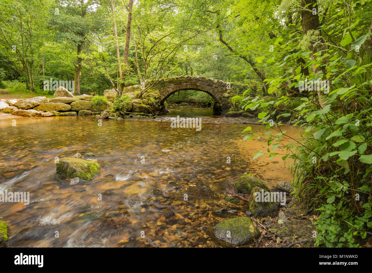 An image of an ancient packhorse bridge situated on the river Bovey, Dartmoor, Devon UK. - Stock Image