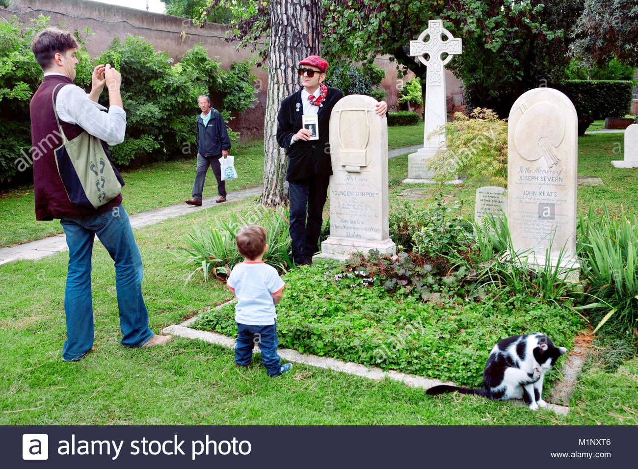 Fan standing / posing next to the grave of British poet John Keats (and English painter Joseph Severn to the right), - Stock Image