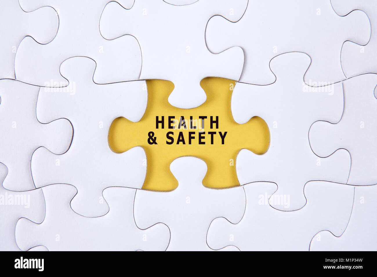 HEALTH AND SAFETY CONCEPT with white jigsaw puzzle - Stock Image