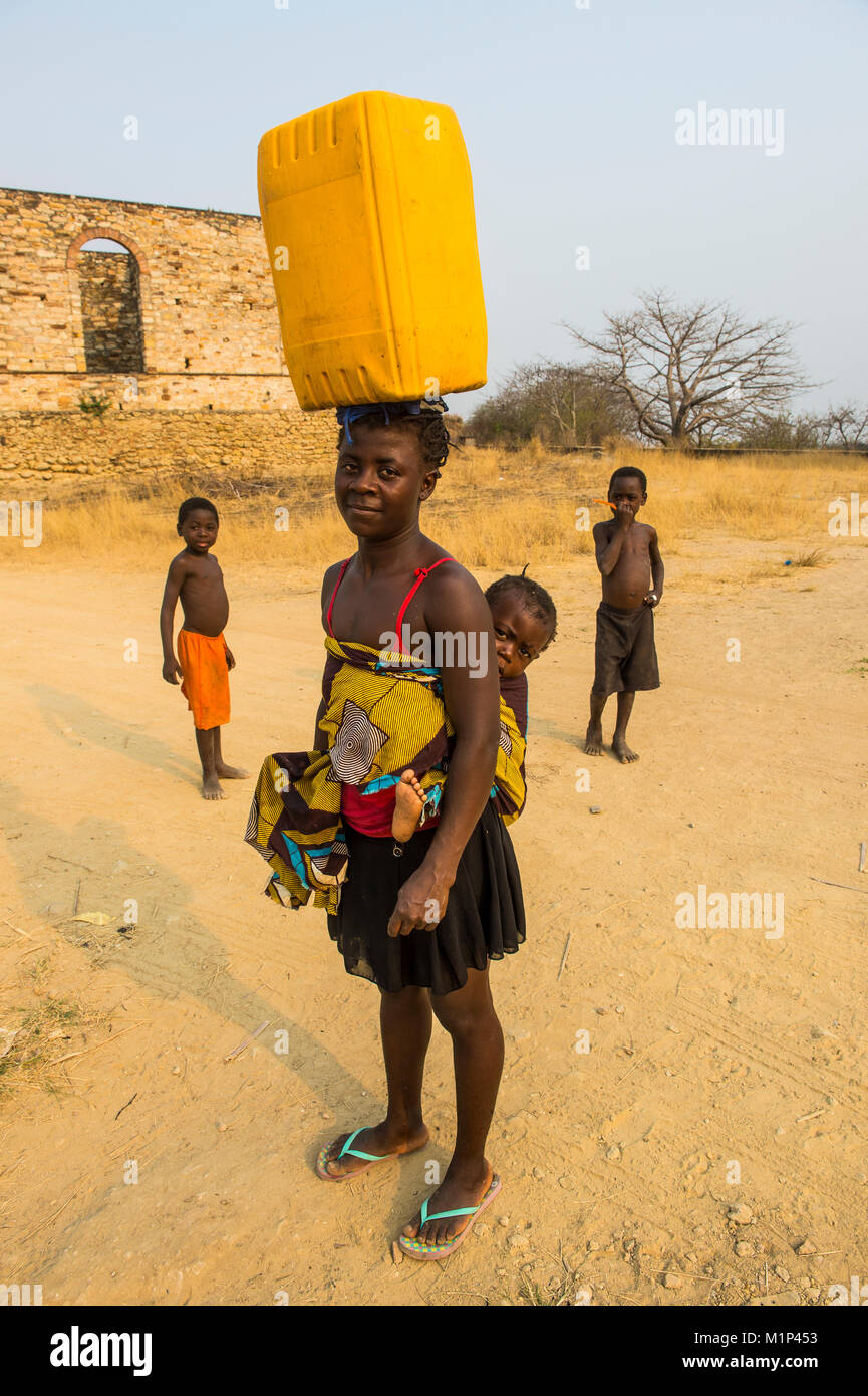 Woman with her baby on her back carrying a water canister on her head, Massangano, Cuanza Norte, Angola, Africa - Stock Image