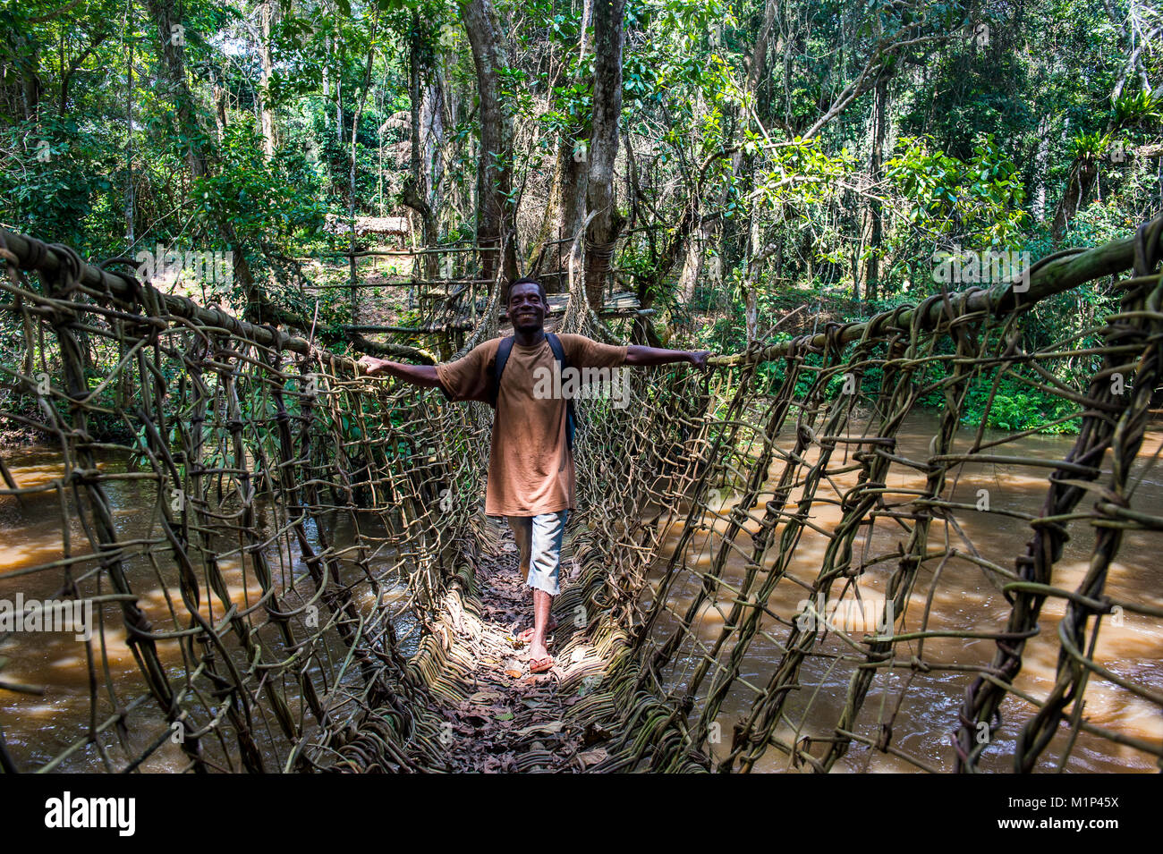 Pygmy walking across a hand made vine bridge in Dzanga-Sangha Park, UNESCO World Heritage Site, Central African - Stock Image