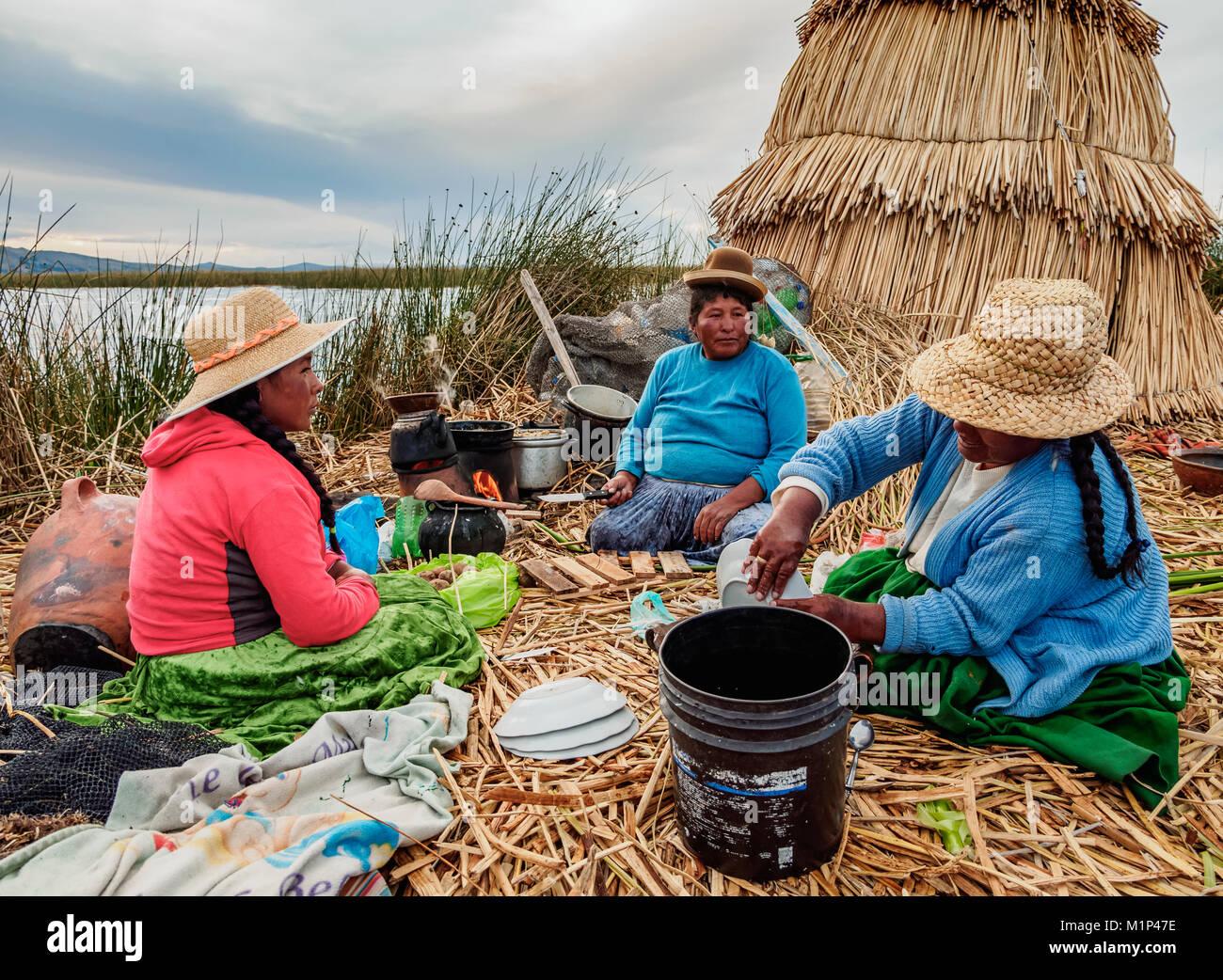 Native Uro Family preparing a meal, Uros Floating Islands, Lake Titicaca, Puno Region, Peru, South America - Stock Image
