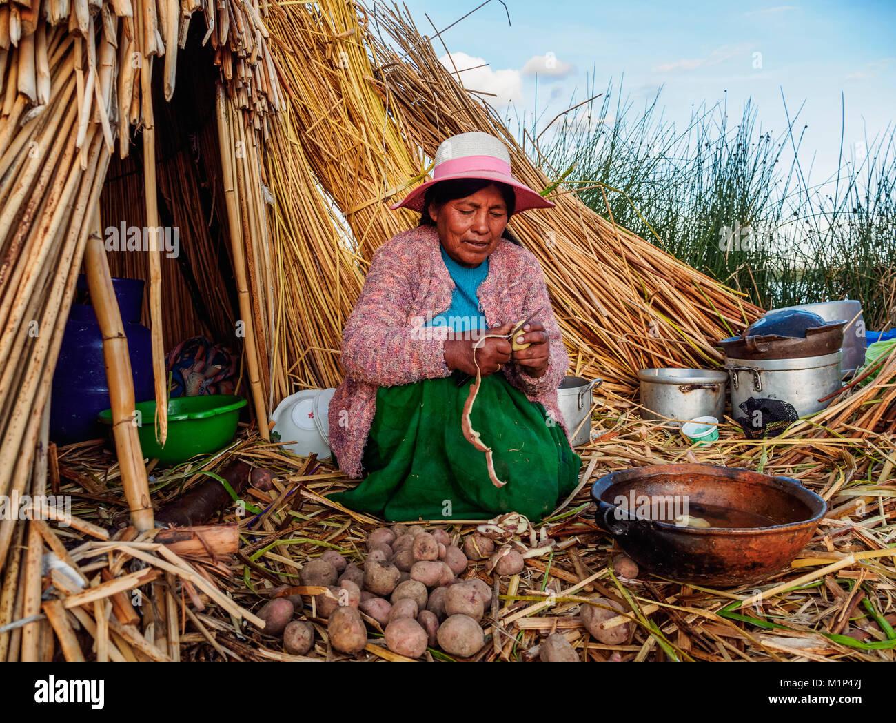Native Uro Lady cooking, Uros Floating Islands, Lake Titicaca, Puno Region, Peru, South America - Stock Image