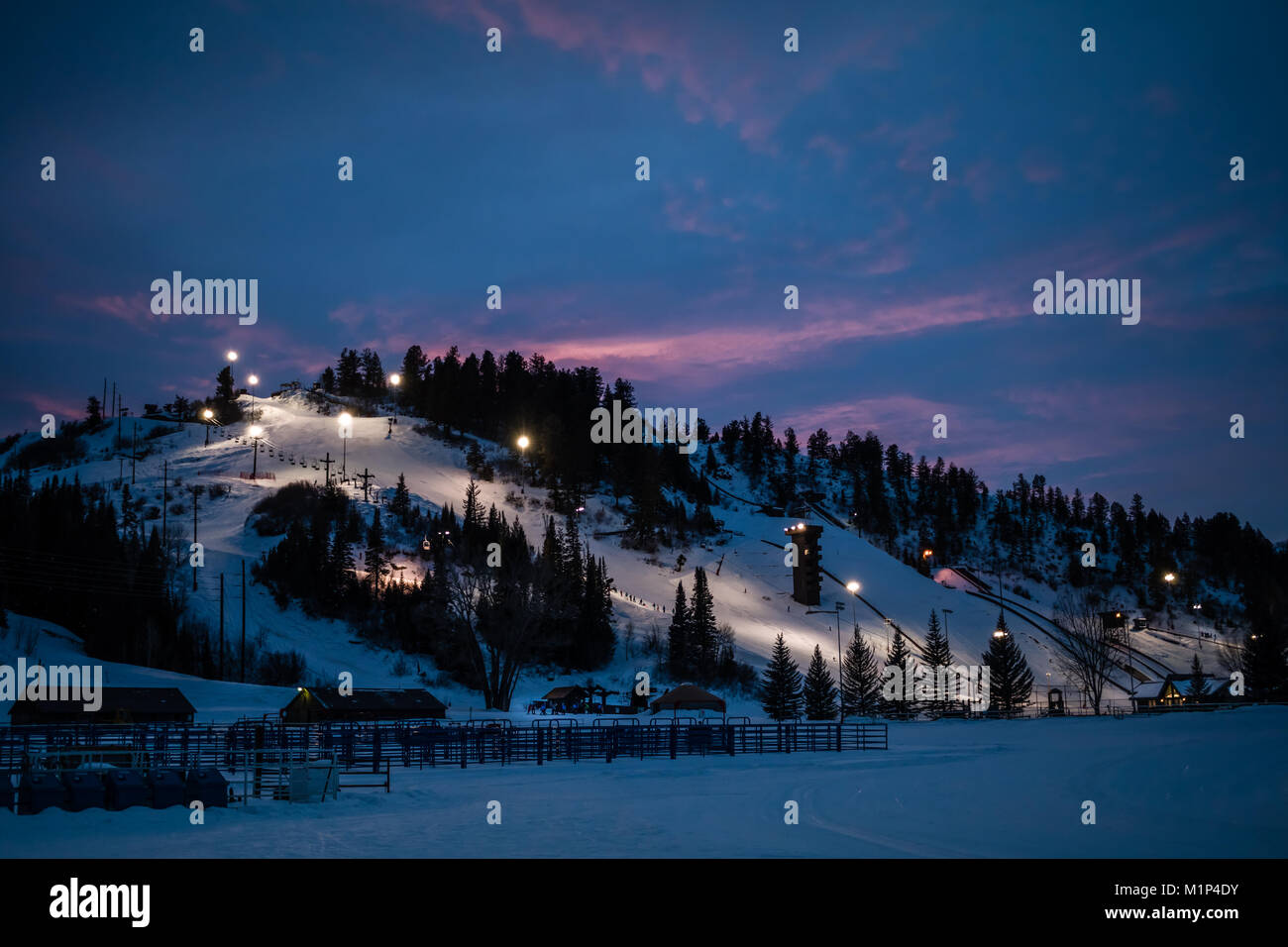 Beautiful view of of a downhill slope lit for night skiing in Steamboat Springs, Colorado, after sunset - Stock Image