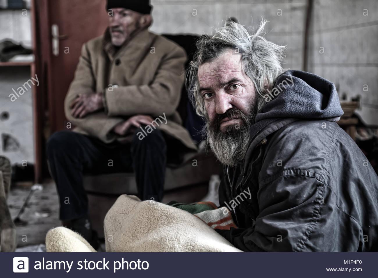 Homeless men sitting in abandoned house - Stock Image