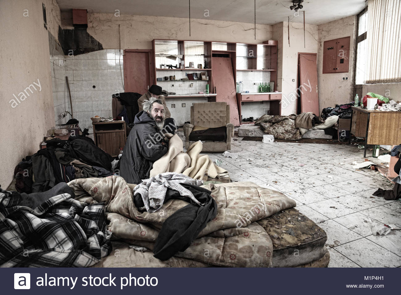 Homeless men sitting in abandoned house - Stock Image
